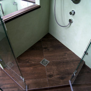 kleiner-duschablauf-eingelassen-in-fliesen-mit-holzoptik